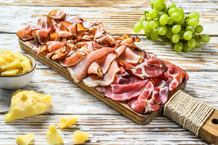 Set of cold cured italian meat Ham, prosciutto, pancetta, bacon. White wooden background. Top view.