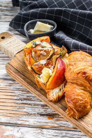 Fresh croissant sandwich with brie cheese, peach and figs. Delicious breakfast. White background. Top view. Reklamní fotografie