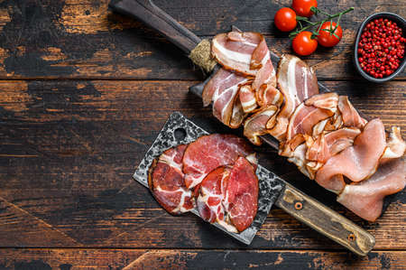 Set of cold cured italian meat Ham, prosciutto, pancetta, bacon. Dark wooden background. Top view. Copy space.