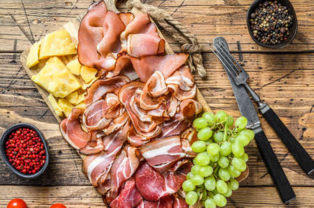 Meat antipasto board, pancetta, salami, sliced ham, sausage, prosciutto, bacon with grape and parmesan cheese. Wooden background. Top view.