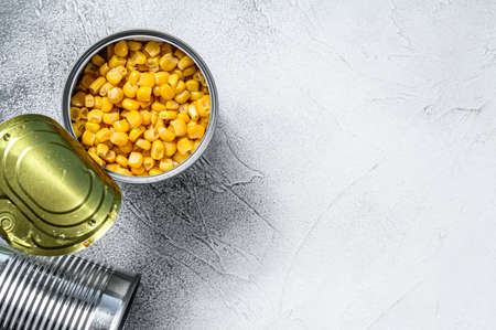 Grains of sweet canned corn in a can. White background. Top view. Copy space.