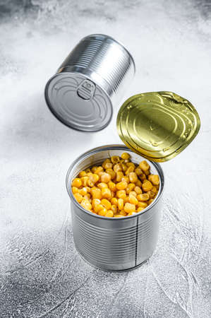 Grains of sweet canned corn in a can. White background. Top view.