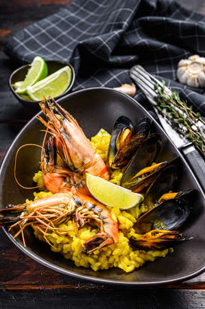 Seafood paella with prawns, shrimps, mussels. Black wooden background. Top view. 免版税图像