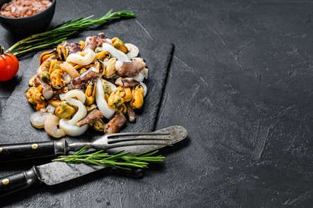Assorted Seafood, mussels, clams, squid, octopus, shrimps and prawn. Black background. Top view. Copy space.