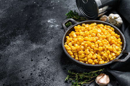 Grains of sweet canned corn in a pan. Black background. Top view. Copy space. Reklamní fotografie