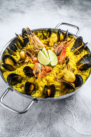 Seafood paella in the fry pan with prawns, shrimps, octopus and mussels. White background. Top view 免版税图像