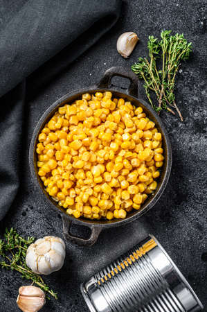 Grains of sweet canned corn in a pan. Black background. Top view. Reklamní fotografie
