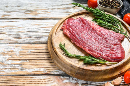 Raw Flank steak on a cutting board. Fresh Marble beef meat black Angus. White wooden background. Top view. Copy space.