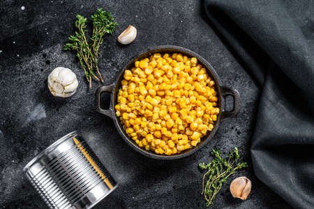 Canned corn in a pan. Canned food. Black background. Top view. Reklamní fotografie