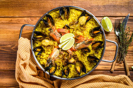 The Spanish paella with seafood prawns, shrimps, mussels in a paellera. Wooden background. Top view.