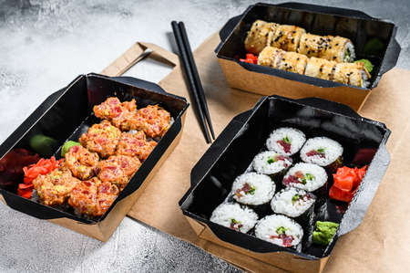 The sushi rolls in the delivery package, ordered in sushi take-out restaurant. Gray background. Top view.