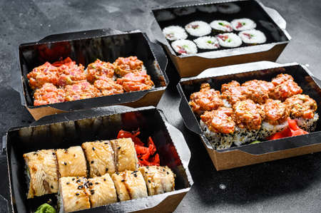 Japanese food concept. Catering, various kinds of sushi rolls set. Black background. Top view.