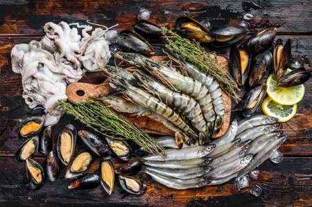 Assorted set of fresh seafood tiger prawns, shrimps, blue mussels, octopuses, sardines, smelt. Dark woodden background. Top view.