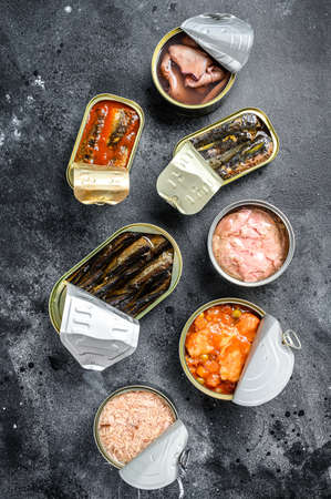 Assortment of cans, canned with different types of fish and seafood. Black background. Top view.