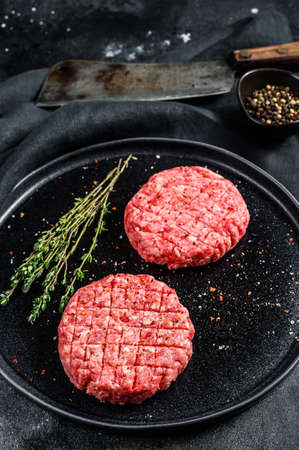 The ground beef patties, minced meat cutlets. Black background. Top view.