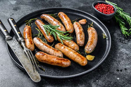 Grilled sausages with rosemary herbs, beef and pork meat. Black background. Top view.