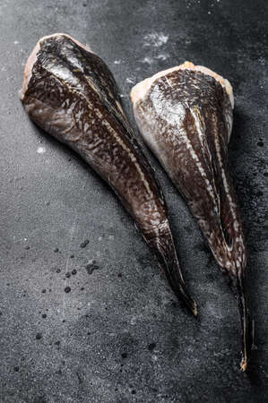 Fresh monkfish without a head. Black background. Top view.