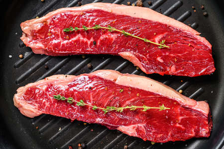 Fresh raw sirloin steak on a grill pan. Gray background. Top view.