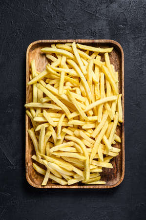 French fries in a wooden bowl. organic potatoes. Black background. Top view. Archivio Fotografico