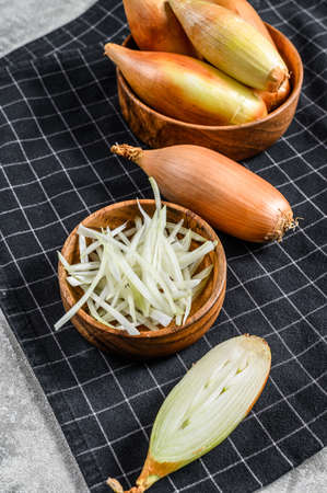 Yellow raw shallot onions, sliced and halved. Gray background. Top view.