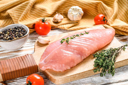 Raw Turkey steaks. Breast fillet with herbs. White wooden background. Top view.