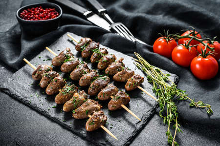 Grilled shish kebab with chicken hearts. Black background. Top view.