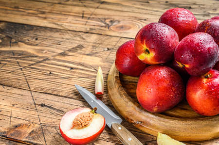 Tray of Fresh red nectarines. Wooden background. Top view. Copy space.