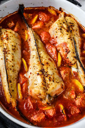 Monkfish baked in tomatoes in a baking dish. Black background. Top view. Stockfoto