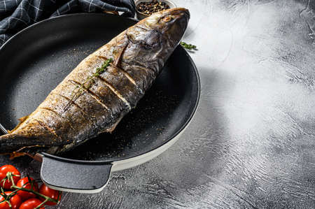 Baked Yellowtail, Japanese amberjack in a pan. Gray background. Top view. Copy space.