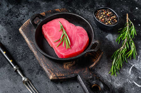 Raw tuna fillet with rosemary in a pan. Black background. Top view.