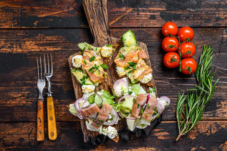 Smoked salmon and herring sandwich with cream cheese and salad on a cutting board. Dark wooden background. Top view.