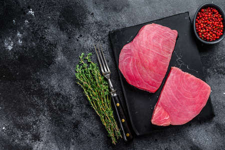 Raw tuna steak on a marble cutting Board. Black background. Top view. Copy space. Stok Fotoğraf