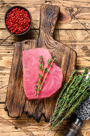 Fresh Raw tuna steak on a wooden cutting Board with knife. wooden background. Top view.