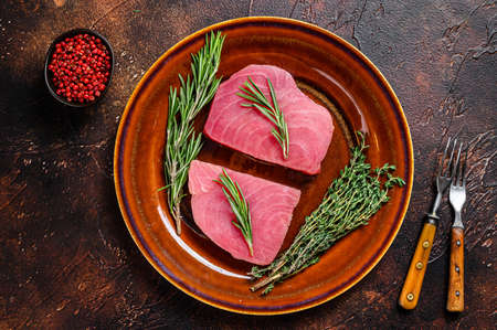 Raw tuna fillet with rosemary and thyme on a plate. Dark background. Top view.