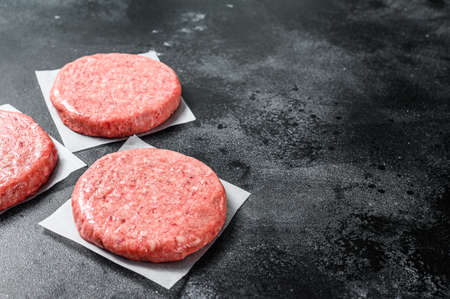 Raw ground meat cutlet, mince beef. Burger patties. Black background. Top view. Copy space. Banco de Imagens