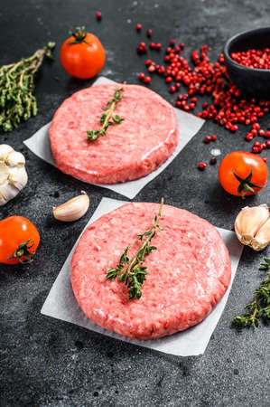Burger patties, raw fresh ground, mince meat. Black background. Top view.