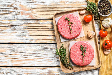 Ground meat patties, raw mince beef. White background. Top view. Copy space.