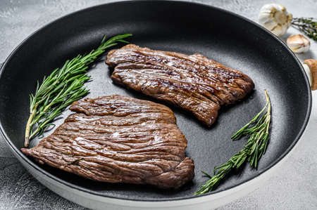 Roasted flat iron and flank steaks. Marble beef meat. Gray background. Top view.