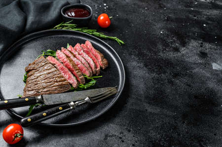 Grilled and cut Flat Iron steak. Marble beef meat. Black background. Top view. Copy space. Stock fotó