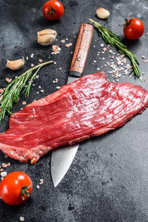 Raw Flank steak black Angus. Fresh Marble beef meat. Black background. Top view.