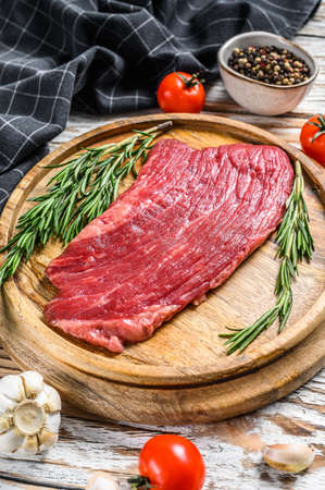 Raw Flank steak on a cutting board. Fresh Marble beef meat black Angus. White wooden background. Top view.