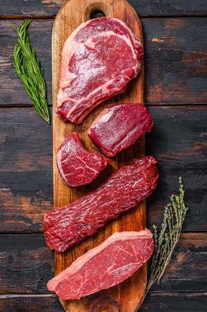 Assortment of raw beef steaks Tenderloin fillet mignon, ribeye, Striploin or new york, skirt, machete. Wooden dark background. Top view.