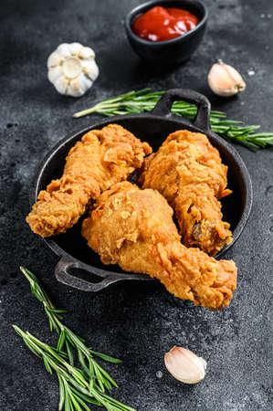 Spicy Deep Fried Breaded Chicken drumsticks. Black background. Top view.
