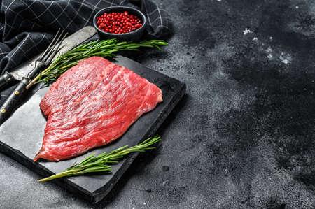 Flat iron steak. Raw Marble beef meat black Angus. Black background. Top view. Copy space. Stock fotó