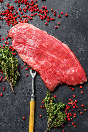 Raw Flank steak with rosemary and pink salt. Fresh Marble beef meat black Angus. Black background. Top view.