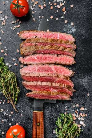 Grilled and sliced flat iron rare steak. Marble beef meat. Black background. Top view.