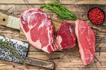Variety of raw black angus beef meat steaks fillet Mignon, rib eye or cowboy, Striploin or new york. Wooden background. Top view. Stock fotó