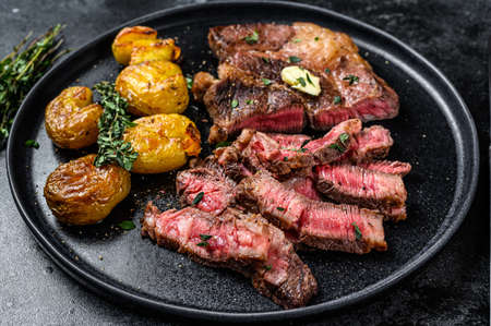 Cut Grilled rib eye beef meat steak with potato. Black background. Top view.