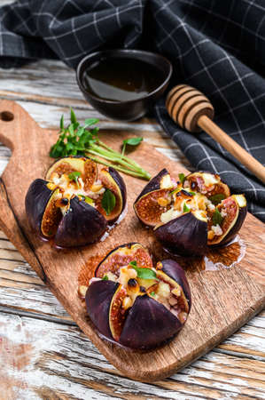 Oven-baked figs with gorgonzola, herbs and honey. White background. Top view.