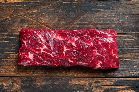 Raw machete or skirt beef steak. Dark wooden background. Top view.